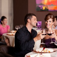 romantic young couple at restaurant table toasting