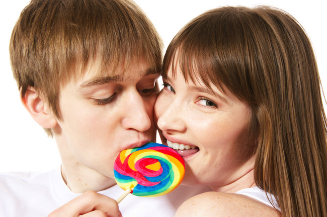 A young teenage couple shares a lollipop